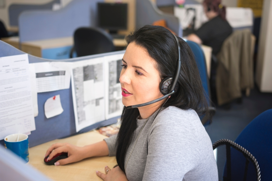 Operator woman talking on headset at work