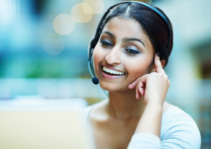 Female customer service representative using headset and laughing