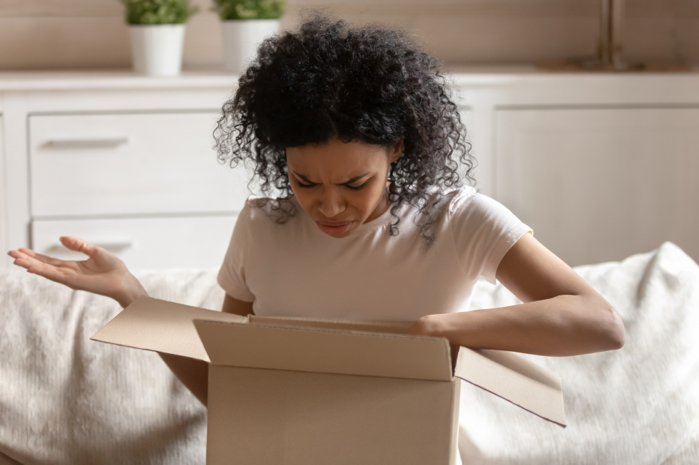 Angry african woman unpack carton box feels irritated