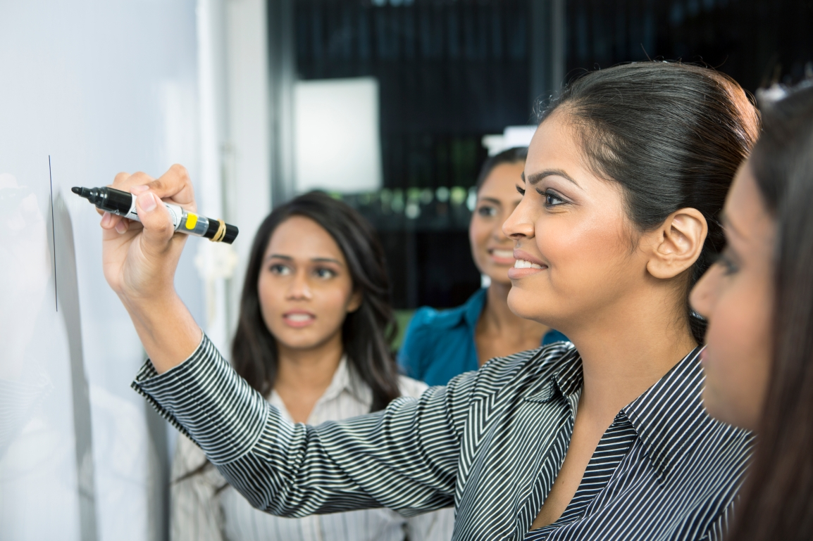 A close-up image of a young Indian business woman and her colleagues standing in front of a whiteboard. The woman is smiling and writing on the board while the others look on.